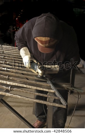 metal worker finishing welds with a grinder - stock photo