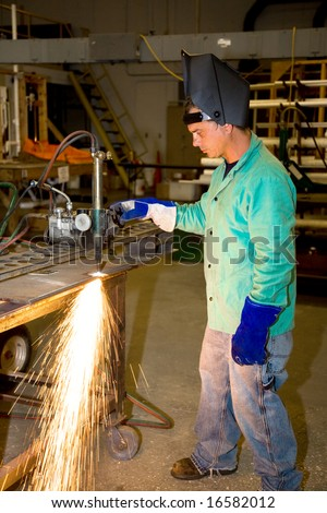 Metal worker in a factory using a track burner to cut a piece of metal.  Authentic and accurate content depiction with all work being performed according to industry code and safety standards. - stock photo