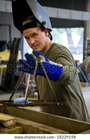 Metal worker in a factory wearing his welding visor. - stock photo
