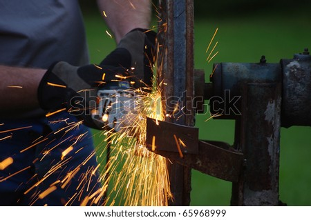 metal worker sawing iron with sparks spreading - stock photo