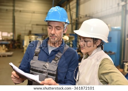 Metal worker showing machine room to apprentice
