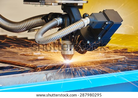 metal working. Plasma or Laser cutting technology of flat sheet metal steel material with sparks - stock photo