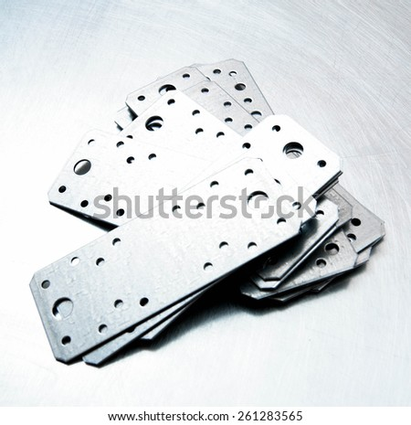 Metal working tools. Metal style. Metal preparations and fixing elements on the scratched metal background. - stock photo