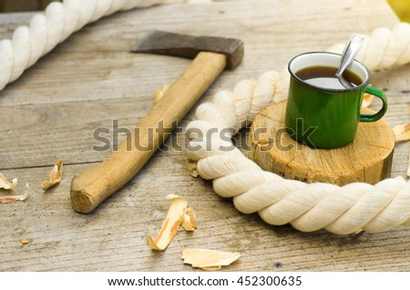 metall cup of tea with axe on wooden background - stock photo