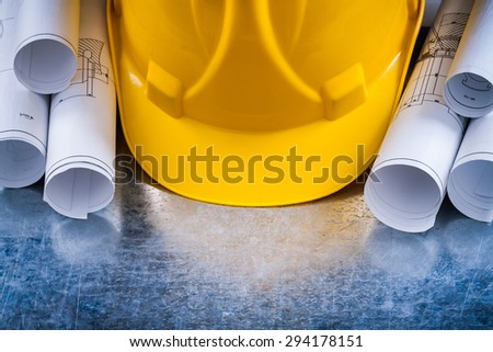 Metallic background with white architectural blueprint rolls and yellow building helmet close up image construction concept. - stock photo
