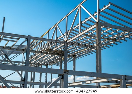 Metallic building construction under blue sky. - stock photo