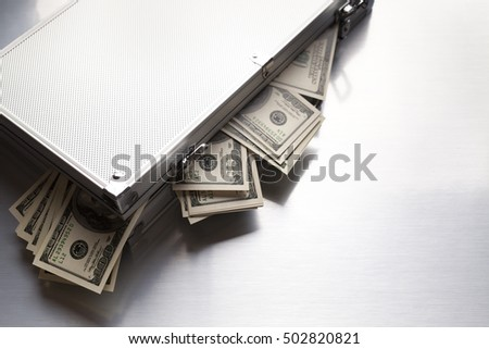 Metallic business suitcase and dollar bills