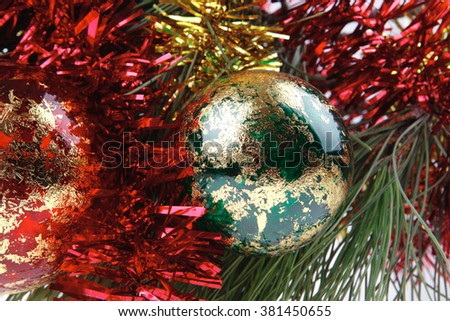 metallic christmas holiday toys with shiny red garland on fir tree twig isolated over white background - stock photo