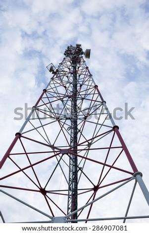 Metallic communication antenna tower with blue, beautiful sky - stock photo