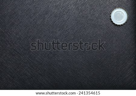 Metallic crown cap  put on black color leather surface background represent the beverage containing equipment - stock photo