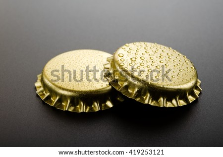 Metallic crown caps on a black background - stock photo
