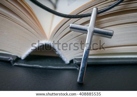 Metallic crucifix and opened Holy Bible. - stock photo