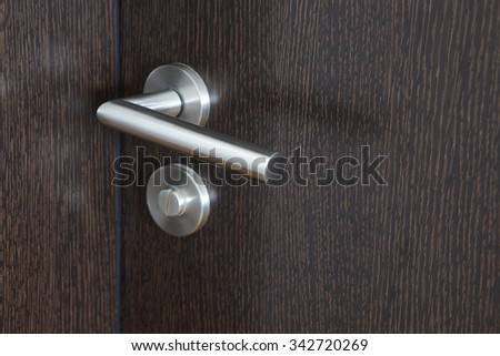 Metallic door knob with lock over a wengue wooden door. Horizontal - stock photo