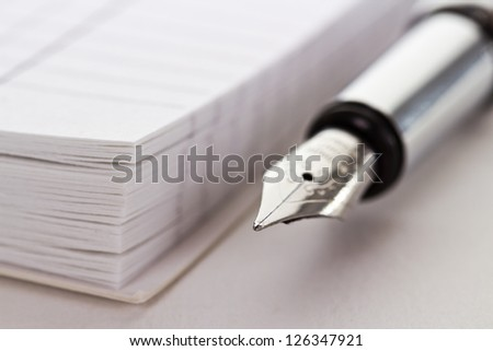 Metallic fountain pen near opened notepad - stock photo