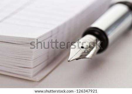Metallic fountain pen near opened notepad - stock photo