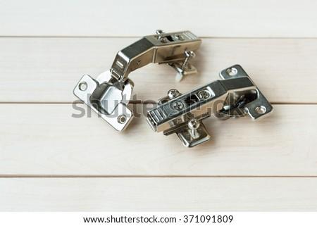Metallic hinge systems lying on a wood background - stock photo