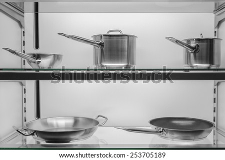 Metallic kitchen cookware in a shop window - stock photo