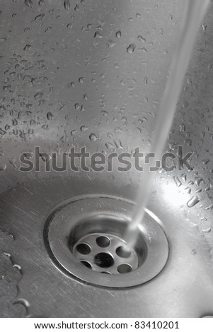 Metallic Kitchen sink with pouring water shot from low angle - stock photo