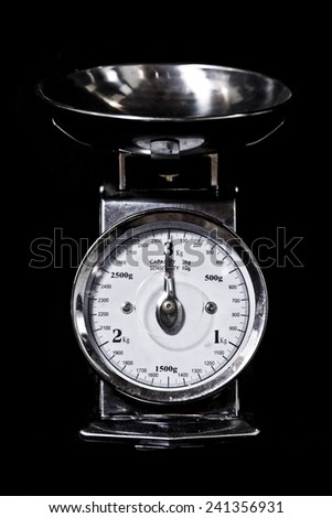 Metallic kitchen weighing scale isolated on black background - stock photo