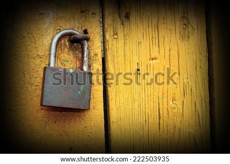 metallic lock on yellow painted wooden door with vignette - stock photo