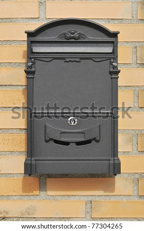 Metallic mailbox in gray placed on the house wall. - stock photo