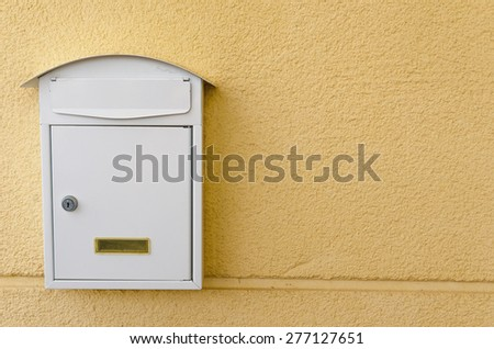 Metallic mailbox painted in white over a yellow background - stock photo