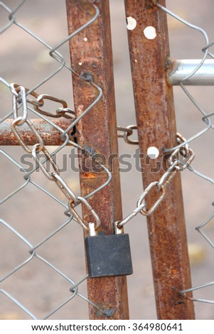 metallic padlock and chain lock at fence door. - stock photo