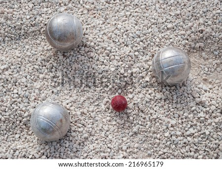 Metallic petanque balls and a small red jack on fine gravel - stock photo