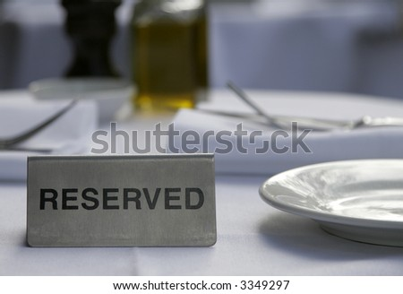 Metallic Silver Reserved Sign On A Restaurant Table