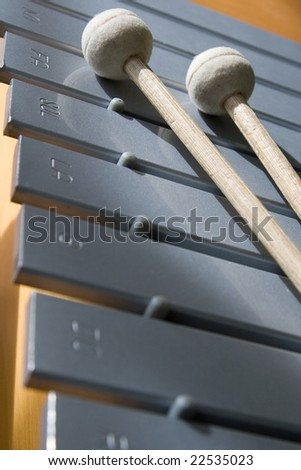 Metallophone with drumsticks and musical notes engraved - stock photo