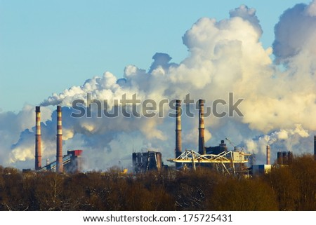 metallurgical plant of pipes and white smoke - stock photo