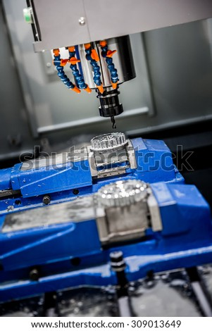 Metalworking CNC milling machine. Cutting metal modern processing technology. Small depth of field. Warning - authentic shooting in challenging conditions. A little bit grain and maybe blurred. - stock photo