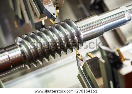 metalworking  industry. cutting tool processing steel metal spiral pinion or worm screw shaft on lathe machine in workshop. Focus on tool. - stock photo