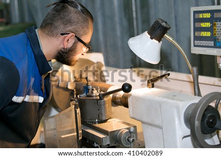 metalworking industry: factory man worker in uniform working on lathe machine in workshop - stock photo