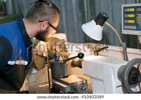 metalworking industry: factory man worker in uniform working on lathe machine in workshop - stock photo