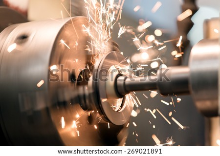 metalworking industry: finishing metal working on lathe grinder machine with flying sparks - stock photo
