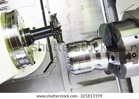 metalworking  industry: multi cutting tool pefroming facing cut of metal detail on lathe machine in workshop