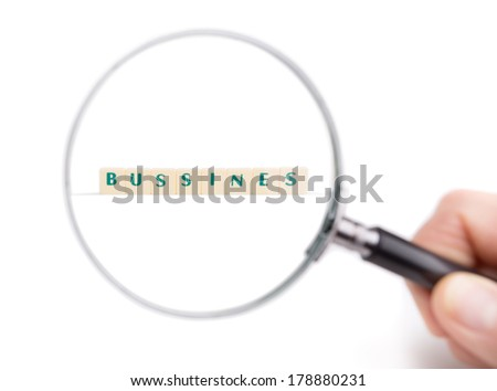 Metaphor Magnifier enlarges the word business. In the man's hand.