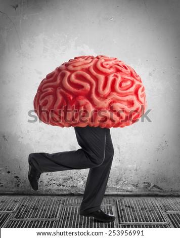 Metaphor of the brain drain. Rubber brain legs while running. - stock photo