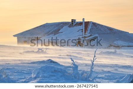 Meteorological station lodge on the mountain Distant Tagangai in Russia during blizzard. - stock photo