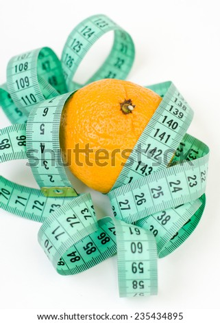 Meter ribbon curling and mandarin closeup isolated - stock photo