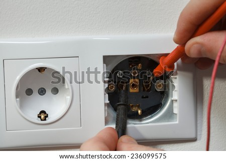 Metering socket voltage with digital multimeter. Installing an electrical plug in a new house. - stock photo