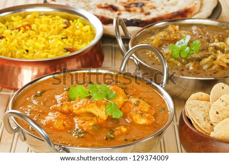 Methi Chicken, or Butter Chicken, with lamb dhansak, pillau rice, naan bread and poppadums. - stock photo