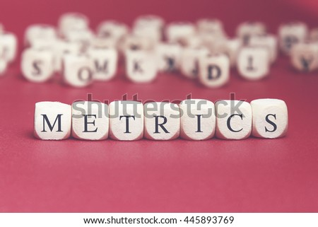 Metrics word written on wood cube with red background - stock photo
