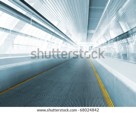 metro escalator in glass corridor - stock photo