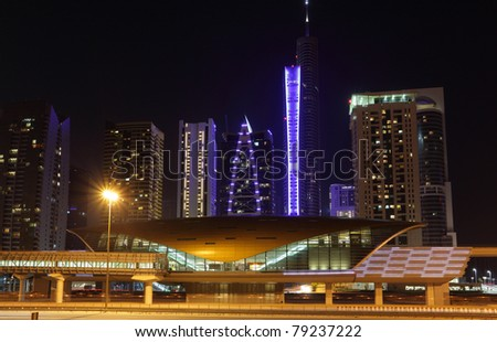 Metro station and Jumeirah Lake Towers at night, Dubai United Arab Emirates - stock photo