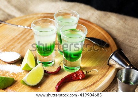Mexican alcoholic cocktail drinks shot on a wooden board. Good tequila cocktail drinks, booze with decor composition with citrus fruits. Different layers of alcohol vodka, liqueur, chasers for drinks. - stock photo