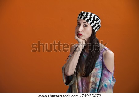Mexican American woman wearing a tie-dye shirt in a miserable mood - stock photo