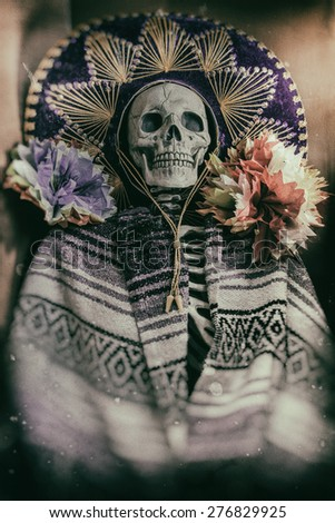"Mexican Bandit Skeleton 4. A skeleton wearing a Mexican sombrero and a poncho, with decorative flowers in a ""Day of the Dead"" decor. Edited in a vintage film style. - stock photo"