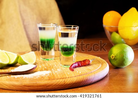 Mexican Bar alcoholic drinks shot on a wooden board. Good tequila drinks or booze with decor composition with citrus fruits. Different layers of alcohol vodka, liqueur, whiskey and chasers for drinks. - stock photo